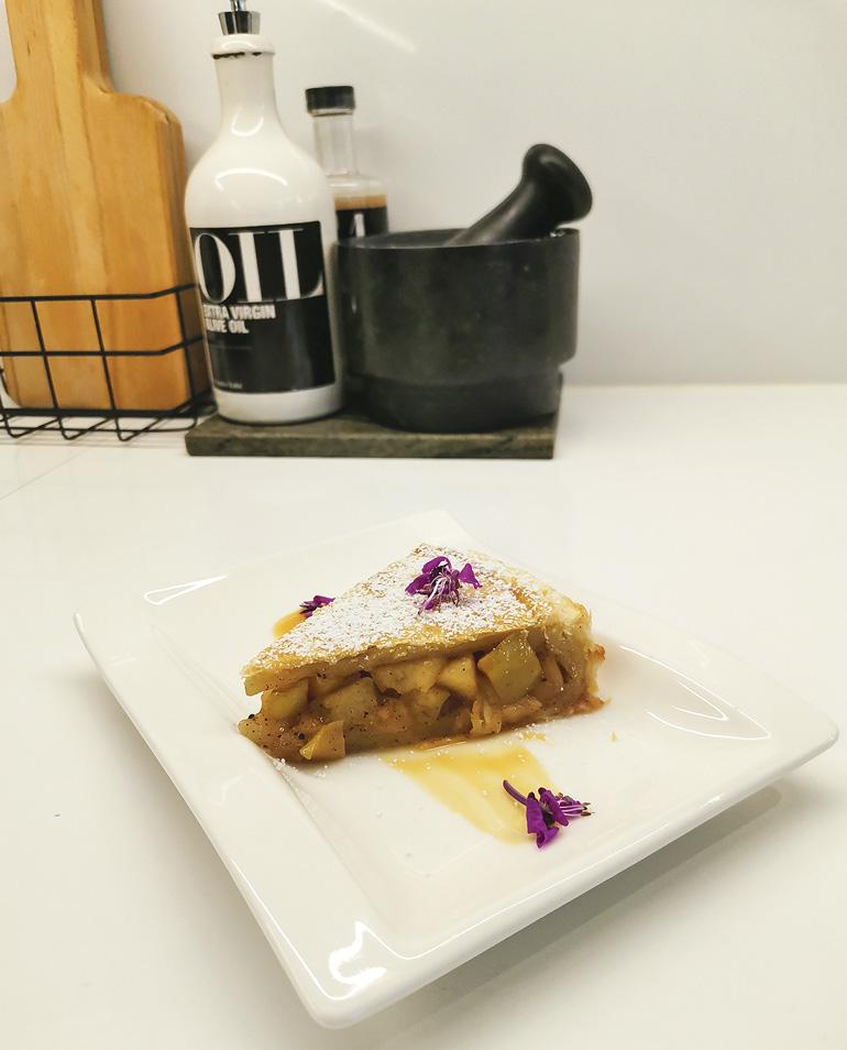 Jälkiruokalautasella omenakakkupala kinuskikastikkeen ja tomusokerin kera.