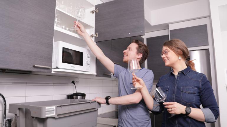 Veera ja Jani purkavat laseja muuttolaatikosta ja asettelevat niitä keittiön kaappiin