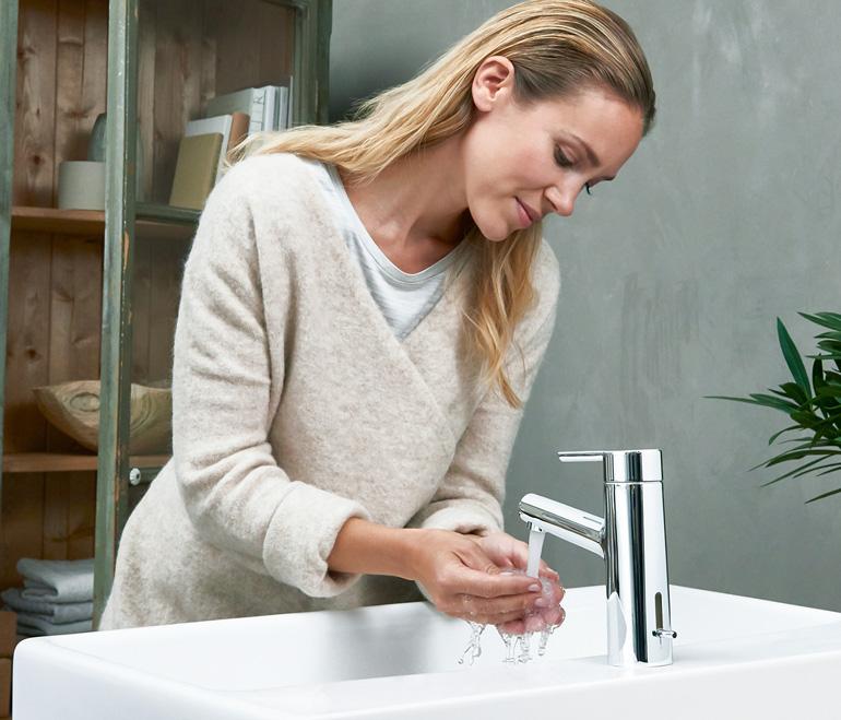 nainen pesee käsiään kylpyhuoneessa