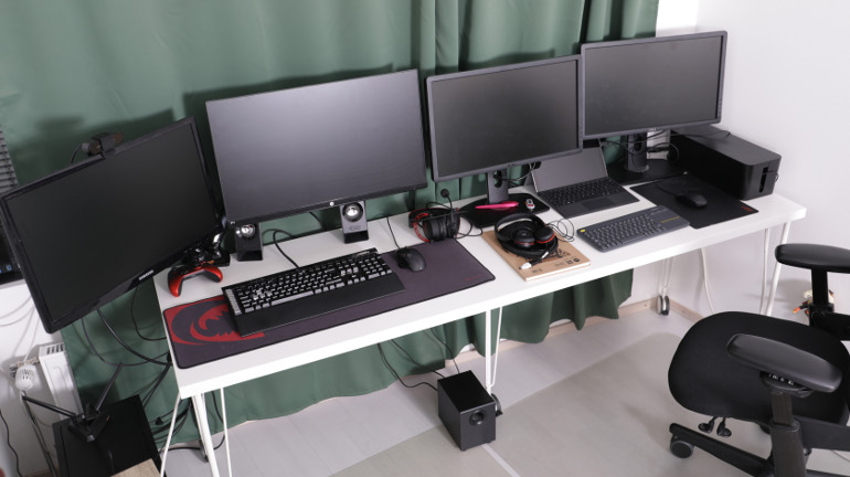 Neljä tietokonenäyttöä rinnakkain pitkällä pöydällä ikkunan edessä.