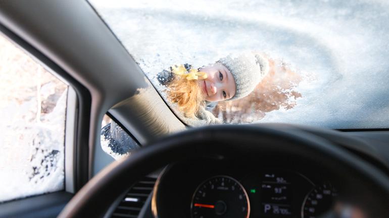 Jäinen tuulilasi, lapsi kurkkii auton sisään